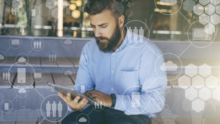 Young_bearded_hipster_man_sits_and_uses_digital_tablet._In_foreground_are_virtual_icons_with_people,_clouds,_digital_gadgets._Guy_blogging,_chatting,_working_online._Social_media._Lifestyle.