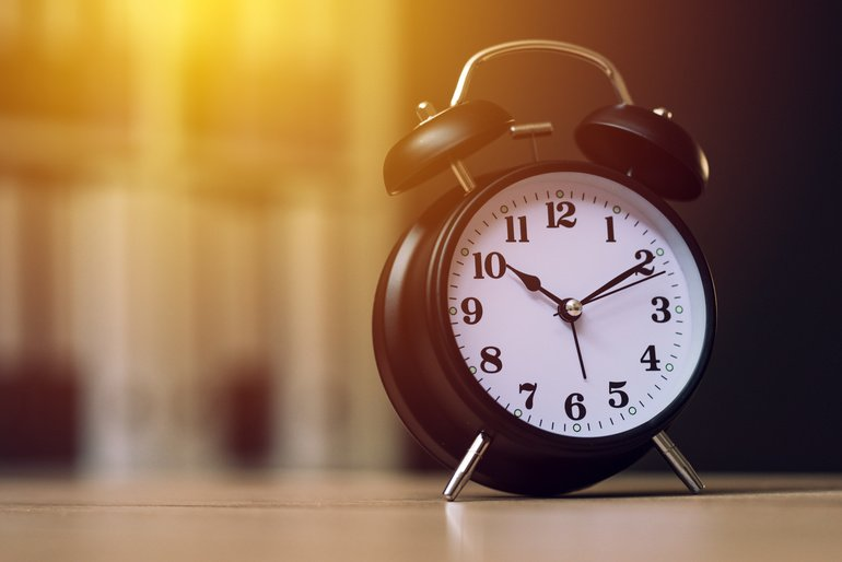 Classic_alarm_clock_showing_time_during_working_hours_or_work_break_in_business_office,_selective_focus