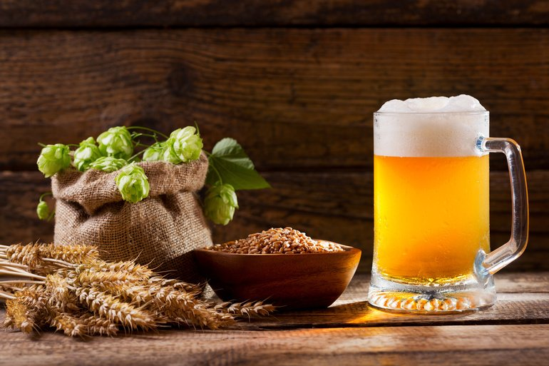 Mug_of_beer_with_green_hops,_wheat_ears_and_grains_and_on_wooden_table