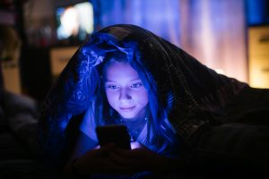 Little_girl_in_bed_under_a_blanket_looking_at_the_smartphone_at_night.