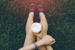 Sport_young_asian_woman_sitting_on_grass,_drinking_coffee._Resting_Runner._Vintage_filter.