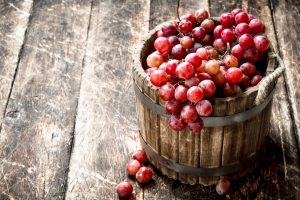 Red_grapes_in_a_wooden_bucket._On_a_wooden_background.
