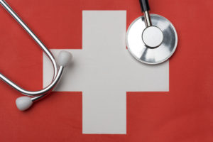 Swiss_flag_and_stethoscope._The_concept_of_medicine._Stethoscope_on_the_flag_in_the_background.
