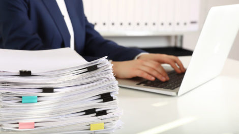 Stack_of_documents_and_woman_working_with_laptop_at_table_in_office,_closeup