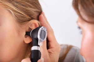 Close-up_Of_Doctor_Checking_Happy_Girl's_Ear_With_Otoscope;_Shutterstock_ID_1246981141