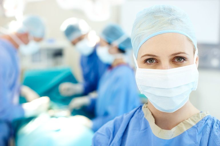 Portrait_of_a_female_surgeon_wearing_a_face_mask_and_hospital_scrubs_in_an_operating_room_-_Copyspace