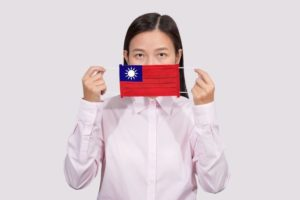 Asian_woman_wearing_hygienic_face_mask_painting_Taiwan_flag_to_protect_from_the_Coronavirus_2019_(COVID-19)_infection_outbreak_situation,_the_virus_originated_from_Wuhan,_China.