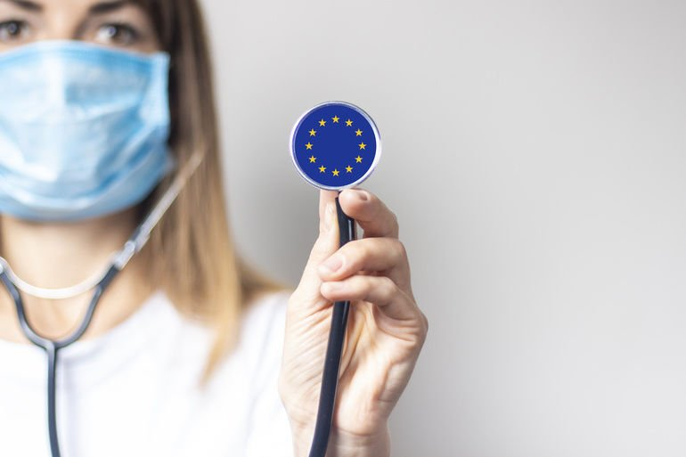 Young_woman_in_a_medical_mask_holds_a_stethoscope_with_the_flag_of_European_Union_on_a_light_background._Concept_of_medicine,_virus,_epidemic,_vaccination.