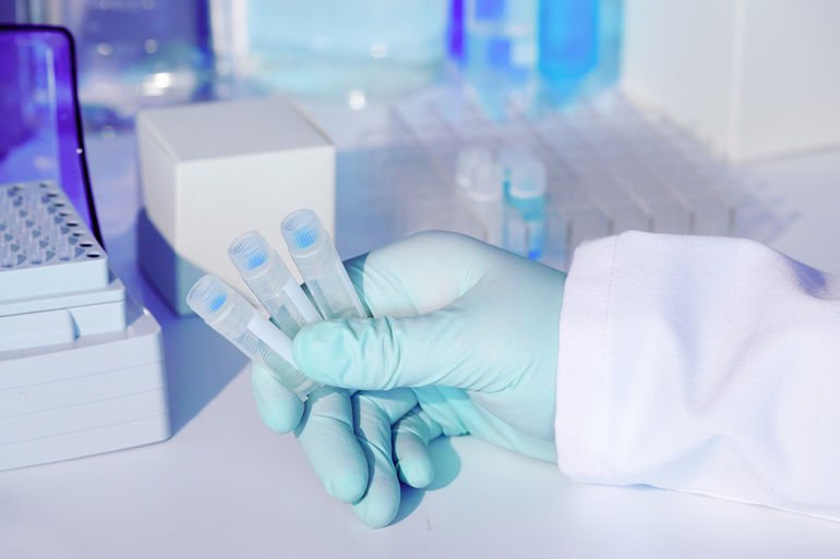 Test_kit_to_detect_presence_of_RNA_virus_in_patient_samples._RT-PCR_kit_reagents_convert_viral_RNA_to_DNA_and_amplify_unique_region_specific_for_virus._Hand_in_glove_holding_test_tubes.