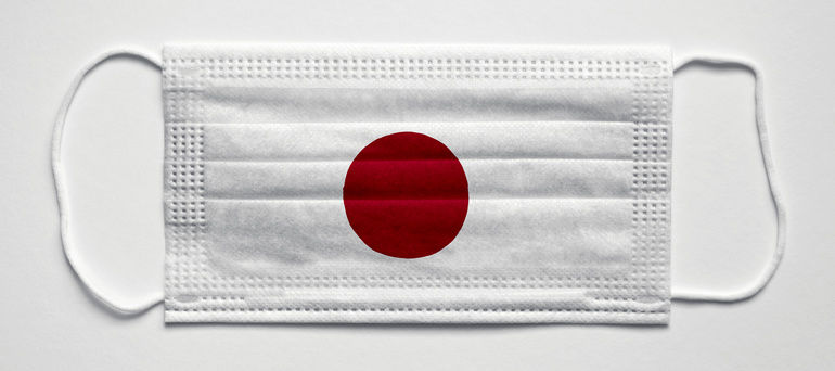 Japan_flag._PANDEMIA._Medical_mask,_Medical_protective_mask_on_a_white_background.Healthcare_and_medical_concept.