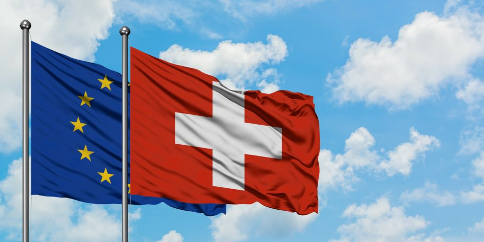 European_Union_and_Switzerland_flag_waving_in_the_wind_against_white_cloudy_blue_sky_together._Diplomacy_concept,_international_relations.