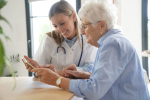 Elderly_woman_with_nurse_at_home_looking_at_tablet
