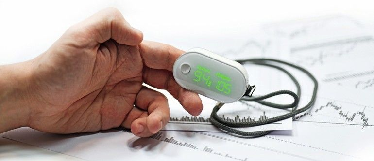 Blood_oxygen_meter_on_mans_finger._Isolated_on_white_background.