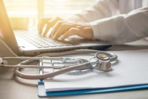 Stethoscope_on_prescription_clipboard_and_Doctor_working_an_Laptop_on_desk_in_hospital,_Healthcare_and_medical_concept,_vintage_color,_selective_focus