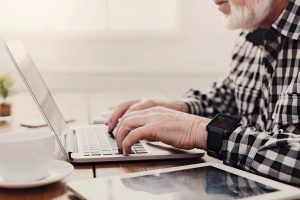 Senior_male_hands_on_laptop_closeup._Unrecognizable_bearded_mature_man_typing_on_computer_keyboard