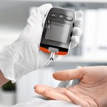Doctor_testing_patient's_glucose_level_with_digital_glucometer_on_blurred_background._Diabetes_monitoring