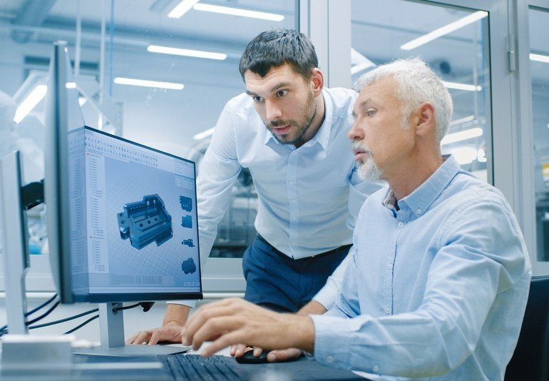 Industrial_Designer_Has_Conversation_with_Senior_Engineer_While_Working_in_CAD_Program,_Designing_New_Component._He_Works_on_Personal_Computer_with_Two_Monitors.