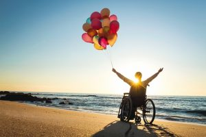 Handicapped_man_on_a_wheelchair_with_colored_balloons_at_the_beach