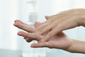 Female_hands_using_wash_hand_sanitizer_gel_pump_dispenser._Clear_sanitizer_in_pump_bottle,_for_killing_germs,_bacteria_and_virus.