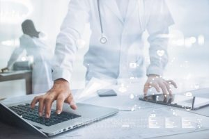 Medicine_doctor_with_stethoscope_touching_icon_medical_network_connection_on_laptop_and_tablet_with_modern_virtual_screen_interface,_medical_technology_network_concept