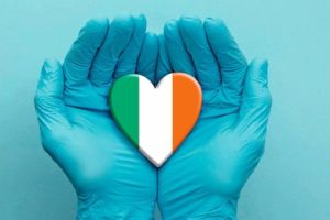 Doctors_hands_wearing_surgical_gloves_holding_Ireland_flag_heart.