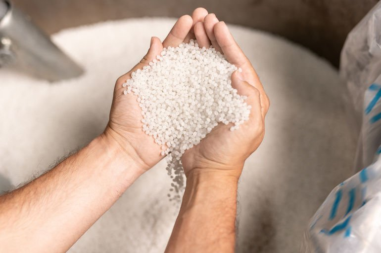 View_of_modern_factory_worker_hands_holding_pile_of_white_polymer_pellets_during_working_process
