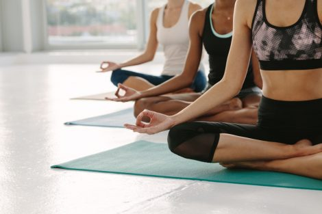 Females_in_gym_class_sitting_on_exercise_mat_with_legs_crossed_and_hands_on_knees._People_meditating_in_Padmasana_yoga_pose_at_class._Cropped_shot_with_focus_on_hands.