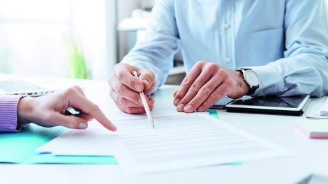 Business_people_negotiating_a_contract,_they_are_pointing_on_a_document_and_discussing_together